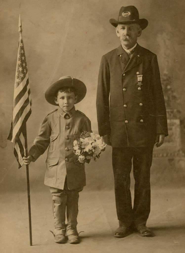 As a young boy, Geoffrey Perrier marched in parades with the Massasoit Fife & Drum Corps. of Plymouth, led by his father, Geoffrey Perrier, Sr. He is pictured here with a Civil War veteran wearing the regalia of the Grand Army of the Republic, ca. 1905.
