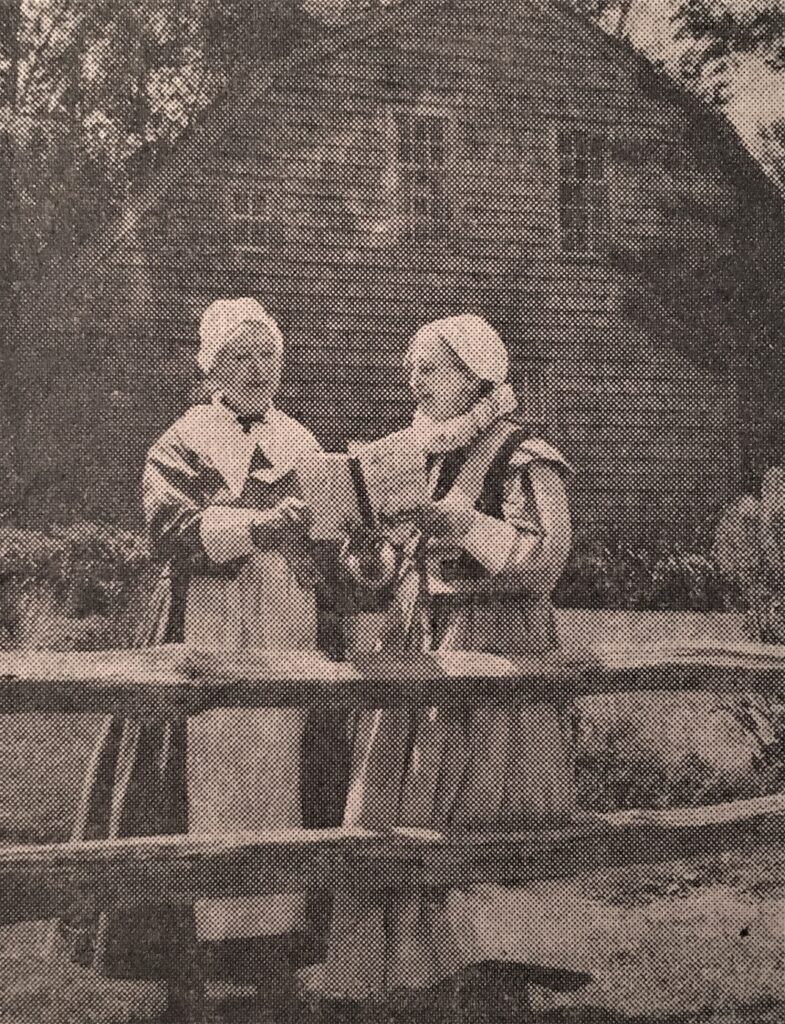 Edith Stinson Jones (left) and Elizabeth St. John Bruce (right) outside the Harlow House with The Plimoth Colony Cook Book; this photograph was printed in the Boston Globe on June 23, 1958. (PAS Archives)