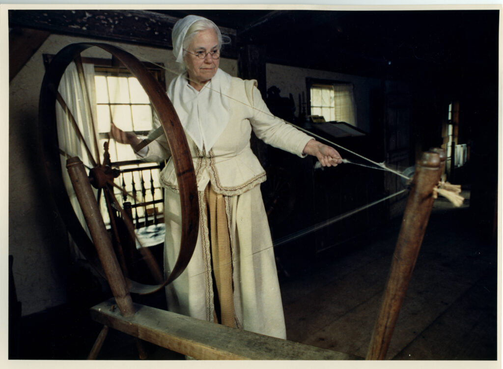 For many years Joann Doll demonstrated spinning at the Harlow House. Here she uses the walking wheel in 1990.